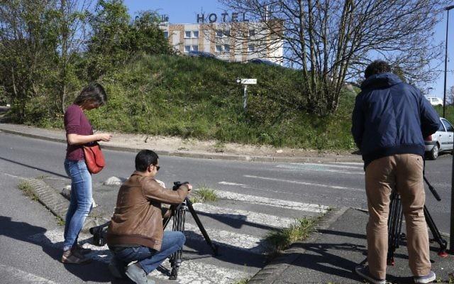 Des journalistes filment le site où le corps d'une femme avec trois blessures par balles a été retrouvé dans une voiture en feu à Villejuif, dans la banlieue sud de Paris, le 19 avril 2015. Les pompiers, prévenus par des passants qui ont vu la voiture en feu, sont arrivés sur les lieux et ont retrouvé le corps sans vie d'une femme âgée d'une trentaine d'année sur le siège passager à l'avant de la voiture en feu. La cause du décès n'a pas encore été établie. (Crédit : AFP PHOTO / FRANCOIS GUILLOT)