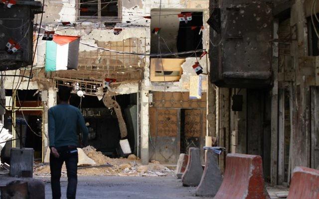 Une photo prise le 23 juin 2014 d'un homme marchant près d'un bâtiment criblé de balle dans le camp de réfugiés palestiniens de Yarmouk à Damas (Crédit : AFP PHOTO / LOUAI BESHARA)