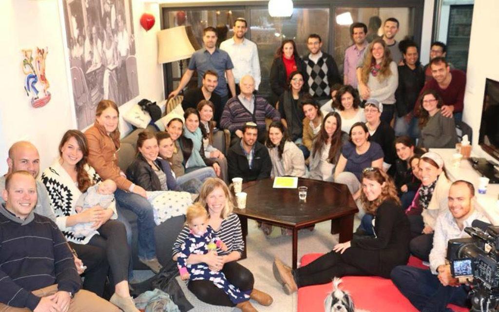 Les jeunes gens se réunissent pour écouter le témoignage du survivant de l'Holocauste Tzvi Ben Porat (deuxième à gauche, deuxième ligne à l'arrière) lors de l'événement 'Zikaron Basalon ' à la maison de la famille Malhi à Jérusalem, le 15 avril 2015 (Crédit : Noam Feiner)