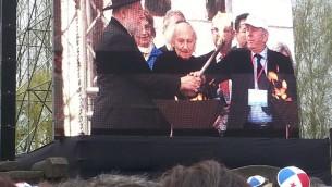 Le grand rabbin Lau allume une des torches en compagnie de Noah Krieger, un rescapé des camps d'origine française devenu un célèbre journaliste israélien (crédit : N.K.)