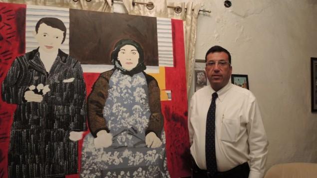 Kevork Nalbandian, un avocat et un travailleur social qui fait parti du comité de planification pour le 100e anniversaire à Jérusalem, se trouve dans sa maison à côté d'une peinture réalisée par un adolescent arménien de 17 ans qui aborde le thèmes de la mémoire et de l'identité arménienne (Crédit : Melanie Lidman / Times of Israël)
