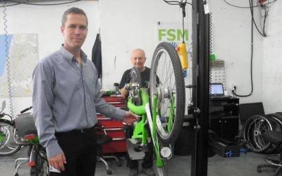 Ofer Sela, le PDG de FSM, un conglomérat d'entreprises qui gère Tel-O-Fun, avec un mécanicien de vélo à Tel Aviv. (Crédit : Melanie Lidman / Times of Israël)