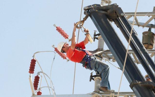 Un employé de la Corporation électrique israélienne. Illustration. (Crédit : Roni Schutzer/Flash90)