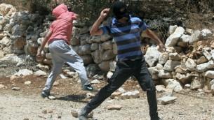photo de Palestiniens masqués qui jettent des pierres en Cisjordanie, le 28 juin 2013 (Crédit : Issam Rimawi / Flash90)
