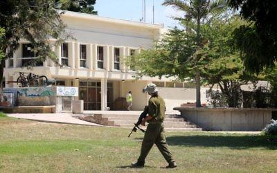 Un soldat israélien se promenant dans le kibboutz Nahal Oz  temporairement abandonné dans le sud d'Israël, alors que les terroristes du Hamas à Gaza continuent de tirer des roquettes sur Israël au 34ème jours de l'opération Bordure protectrice, le 10 août 2014 (Crédit : Edi Israël / Flash90)