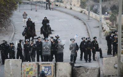 La police des frontières israélienne monte la garde à côté de nouveaux blocs de ciment placés à l'entrée d'Issawiya à Jérusalem-Est lors d'une manifestation contre la fermeture du quartier, le 12 novembre 2014 (Crédit : Hadas Parush / Flash90)