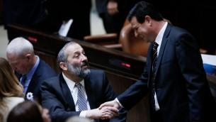 Le chef du parti Shas Aryeh Deri serre la main au chef de liste arabe unie Ayman Odeh lors de la cérémonie d'assermentation de la 20e Knesset le 31 mars 2015 (Crédit : Miriam Alster / Flash90)