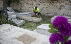 Illustration : Un jeune nettoie le cimetière arménien sur le mont Sion, près du quartier arménien de la Vieille Ville de Jérusalem, le 15 avril 2015 avant les prières qui auront lieu au cimetière en l'honneur des victimes du génocide arménien (Crédit : Hadas Parush / Flash90)