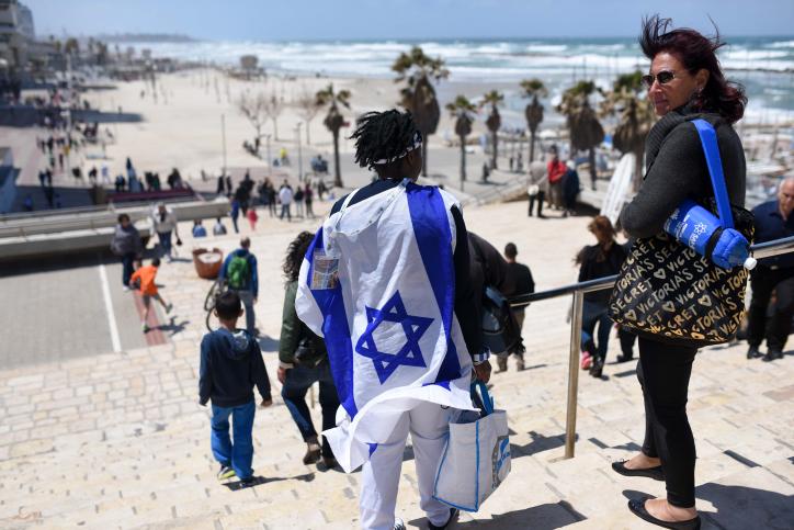 Israéliens regardent une démonstration de l'armée de l'air israélienne le 67e Jour de l'Indépendance d'Israël sur la plage de Tel Aviv le 23 avril 2015. ׂ (Crédit : Ben Kelmer / Flash90)