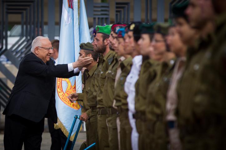 Le président israélien Reuven Rivlin plaisante avec les soldats pendant qu'il inspecte les rangs lors d'une cérémonie exceptionnelle pour les militaires dans le cadre des célébrations du Jour de l'Indépendance d'Israël le 23 avril 2015 à la résidence du président à Jérusalem (Crédit : Miriam Alster / Flash90)