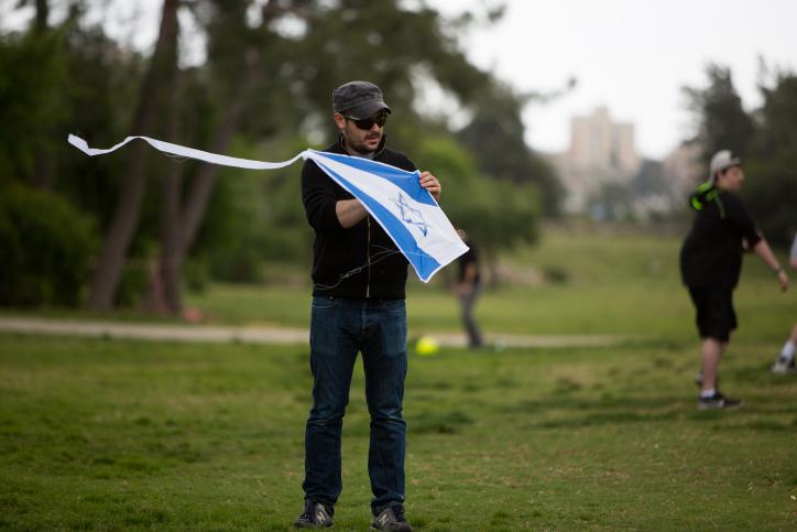 Un Israélien se prépare à faire voler un cerf-volant décoré avec le drapeau israélien au cours des célébrations du Jour de l'Indépendance dans un parc de Jérusalem le 23 avril 2015 (Crédit : Yonatan Sindel / Flash90)