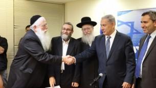 Les chefs de file du Likud, Benjamin Netanyahu, et de Yahadout HaTorah, Yaakov Litzman, se serrent la main, le 29 avril 2015. (Crédit : Autorisation, Likud)