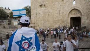 """Un adolescent portant un drapeau israélien avec un autocollant sur lequel il est écrit """"Kahane avait raison"""" se tient devant la porte de Damas à Jérusalem-Est le 8 mai 2013. (Crédit photo: Yonatan Sindel / Flash90)"""
