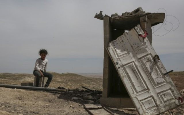 Une jeune fille palestinienne assise à proximité de toilettes dans le village palestinien d'Al Mufakara, près de la route 60, au sud du mont d'Hébron,  en Cisjordanie, le 23 avril 2014. Cette zone avait été déclarée zone militaire fermée par Israël, ce qui rend illégal tout logement. En conséquence, la plupart des habitants vivent ici dans des grottes, par peur des démolitions de maisons (Crédit : Hadas Parush / Flash90)