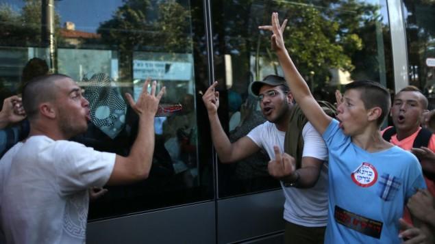 """Des adolescents juifs de droite portant des autocollants qui disent « Kahane avait raison » et """"Vengeance"""" qui font un doigt d'honneur et crient sur les femmes arabes assises à l'intérieur du tram dans le centre de Jérusalem, lors d'une grande manifestation de la droite contre le terrorisme arabe le 1er juillet 2014, en réponse à l'enlèvement et  au meurtre de trois jeunes Juifs (Crédit : Nati Shohat / Flash90)"""