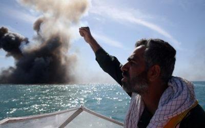 Un membre du corps d'élite iranien des Gardiens de la Révolution scande des slogans après l'attaque d'un navire de guerre pendant un exercice militaire dans le détroit d'Ormuz, au sud de l'Iran, le 25 février 2015. (Crédit : Hamed Jafarnejad/AFP/Fars News)