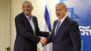 Le chef de file du parti Koulanou Moshe Kahlon et le Premier ministre Benjamin Netanyahu se serrent la main après avoir signé un accord de coalition le 29 avril 2015. (Crédit photo: autorisation/ Likud)