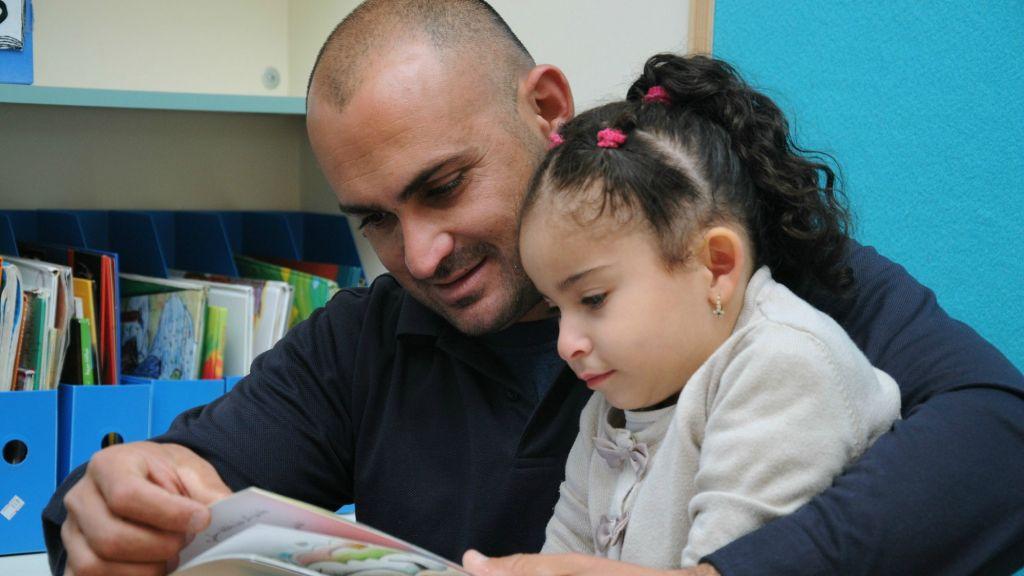 Un père fait la lecture à sa fille à Baqa al-Gharbiyye (Crédit : Akmal Nagnagy)