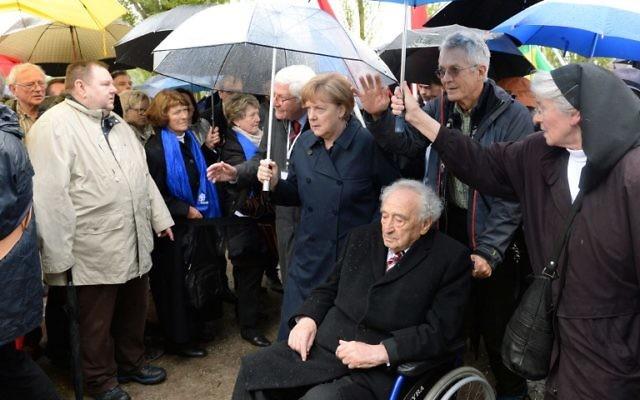 La chancelière allemande Angela Merkel (C) marche avec un survivant de l'Holocauste Max Mannheimer (3ème D) à l'ancien camp de concentration nazi de Dachau, au sud-ouest de l'Allemagne, lors d'une cérémonie marquant les 70 ans de sa libération par les forces américaine, le 29 avril 1945 -  le 3 mai 2015 (Crédit : AFP PHOTO / CHRISTOF STACHE)