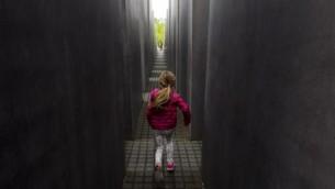 Une jeune fille joue à cache-cache dans le Mémorial dédié aux Juifs assassinés d'Europe, le Mémorial de l'Holocauste, à Berlin le 30 avril 2015. (Crédit : AFP / JOHN MACDOUGALL)
