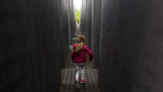 Une jeune fille dans le Mémorial dédié aux Juifs assassinés d'Europe, le Mémorial de l'Holocauste, à Berlin le 30 avril 2015. (Crédit : AFP / JOHN MACDOUGALL)