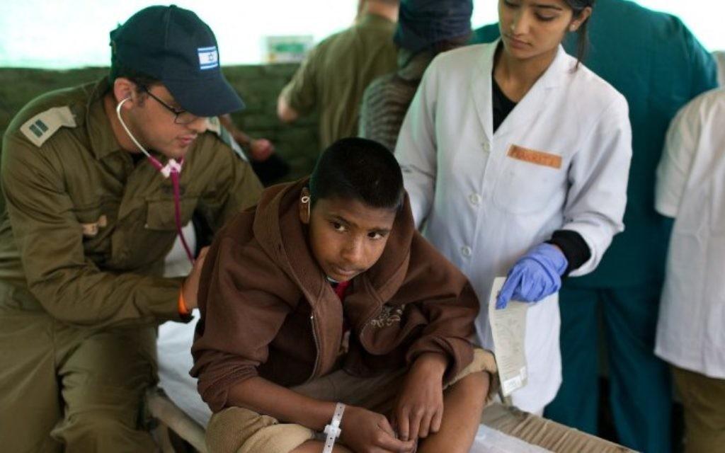 Un médecin militaire israélien soigne un garçon népalais à l'hôpital de campagne israélien de Katmandou, le 30 avril 2015. (Crédit : AFP/Menachem Kahana)