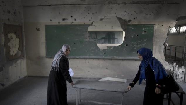 Des enseignantes palestiniennes portent une table dans une salle de classe dans une école du gouvernement dans la ville de Gaza, le 13 septembre 2014, un jour avant les enfants retournent à l'école  (Crédit : AFP / Mahmud Hams)