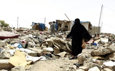 Une Yéménite au milieu des décombres des maisons détruites par une frappe aérienne saoudienne sur une zone résidentielle en avril 2015, dans la capitale Sanaa, le 18 mai 2015. (Crédit : Mohammed Huwais/AFP)