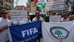 Des Palestiniens qui tiennent des bannières pendant une  manifestation dans le centre de la ville de Ramallah en Cisjordanie, demandant l'expulsion d'Israël de l'organe mondial du football, la FIFA, le 19 mai 2015  (Crédit :AFP PHOTO / ABBAS MOMANI)