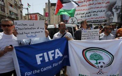 Des Palestiniens qui tiennent des bannières pendant une  manifestation dans le centre de la ville de Ramallah en Cisjordanie, demandant l'expulsion d'Israël de l'organe mondial du football, la FIFA, le 19 mai 2015  (Crédit : AFP PHOTO / ABBAS MOMANI)