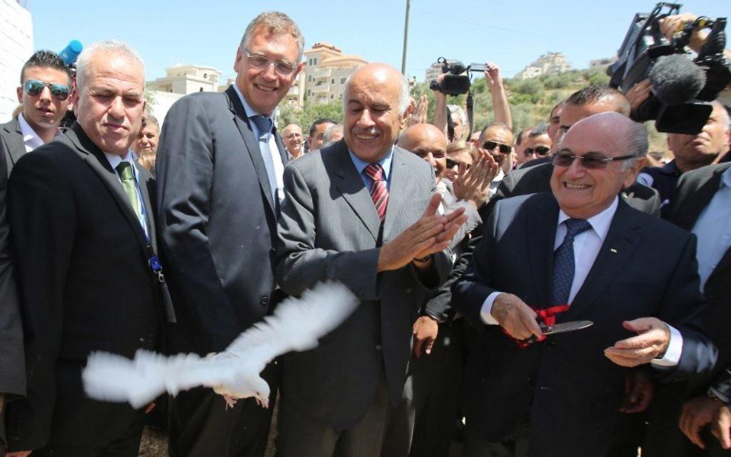 La président de la FIFA, Joseph Blatter (à droite) libère une colombe tandis que le président de l'Association de football palestinien, Jibril Rajoub (au centre) applaudit lors de sa visite au village de Dura al-Qaraa, près de la ville cisjordanienne de Ramallah, le 20 mai 2015. (Crédit : AFP / ABBAS MOMANI)