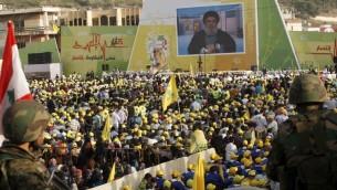 Des partisans du Hezbollah libanais se réunissent dans la ville de Nabatiyeh, le 24 mai 2015, pour assister à un discours télévisé prononcé par Hassan Nasrallah, le chef du mouvement, marquant le 15e anniversaire du retrait israélien du sud du Liban. (Crédit : Mahmoud Zayat / AFP)