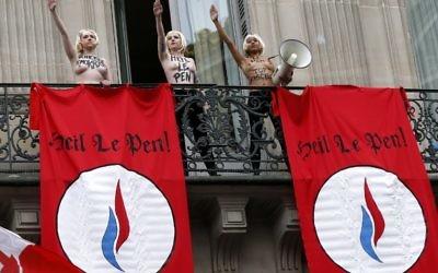 """Des activistes Femen effectuant le salut nazi près de drapeaux où  on peut lire """"Heil Le Pen"""", sur un balcon  lors d'un rassemblement FN en l'honneur de Jeanne d'Arc  juste en dessous du balcon où elles se trouvent à Paris le 1er mai 2015 (Crédit : AFP PHOTO / THOMAS SAMSON)"""