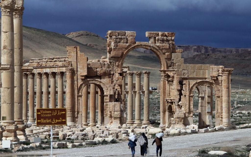 Une photo prise le 14 mars 2014 montre des citoyens syriens marchant dans la ville antique de Palmyre, à 215 km au nord-est de Damas. L'État islamique (EI), qui se vante d'avoir détruit des sites antiques en Irak, menace l'ancien joyau de Palmyre, un site inscrit au patrimoine mondial de l'UNESCO, le 14 mai 2015 (Crédit : AFP PHOTO / JOSEPH EID)