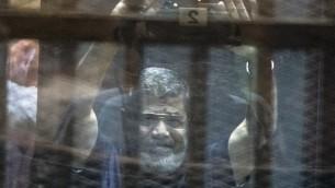 L'ancien président égyptien Mohammed Morsi dans sa cellule, lors de son procès, le 16 mai 2015 (Crédit : AFP)