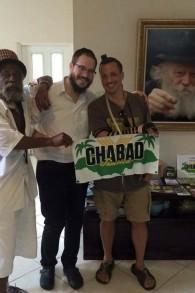 Rabbi Yaakov Raskin (centre) apprend aux hommes la manière de mettre les Téfilines au Chabad House à Montego Bay, en Jamaïque (Crédit : Autorisation)