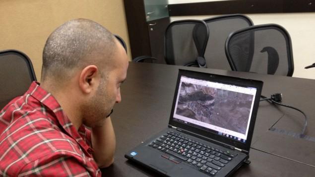 Ovad Arad, le directeur des opérations sur le terrain de Regavim, étudie une carte de la Cisjordanie fournies par l'Administration civile israélienne, le 29 avril 2015 (Crédit : Elhanan Miller / Times of Israël)