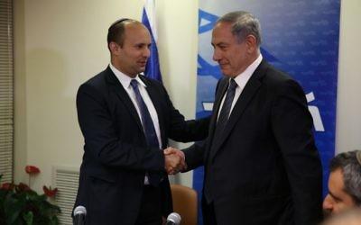 Naftali Bennett et Benjamin Netanyahu se serrent la main après avoir conclu in extremis un accord de coalition (Crédit : new media/Likud)