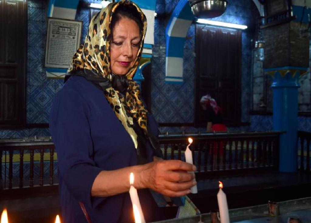 Une femme allume une bougie à la synagogue de la Ghriba en Tunisie (Crédit : AFP)