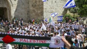 """Des femmes palestiniennes brandissant une écharpe aux couleurs de la Palestine alors que de jeunes israéliens brandissent leur drapeau national dans la """"marche des drapeaux"""" passant devant la porte de Damas, dans la Vieille Ville de Jérusalem lors des célébrations de Yom Yeroushalayim, le 17 mai 2015. (Crédit photo: AFP / Jack Guez)"""