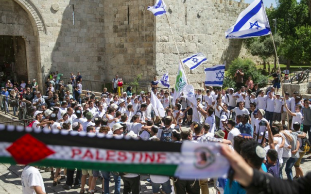 """Des femmes palestiniennes brandissant une écharpe en faveur  de la Palestine alors que de jeunes israéliens brandissent leur drapeau national dans la """"marche des drapeaux"""" passant devant la porte de Damas, dans la Vieille Ville de Jérusalem lors des célébrations de Yom Yeroushalayim, le 17 mai 2015. (Crédit photo: AFP / Jack Guez)"""