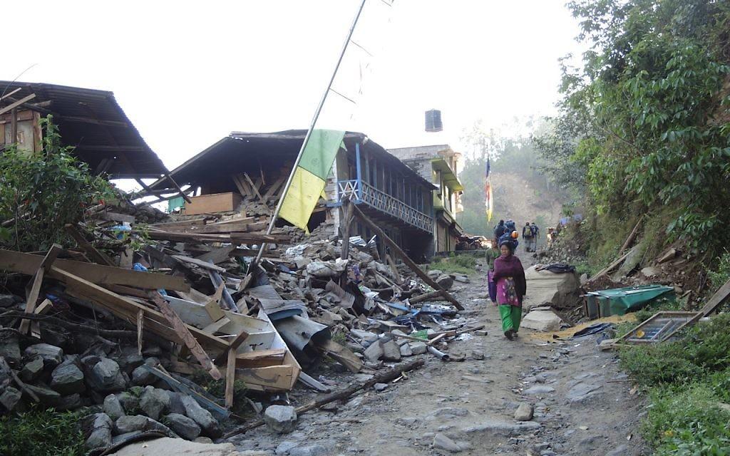 Une femme passe sous un cordon de drapeaux de prière dans le village détruit de Topani, dans le district durement touché de Sidhulpalchowk à 7 heures de route de Katmandou, au Népal, mai 2015 (Crédit : Melanie Lidman / Times of Israël)