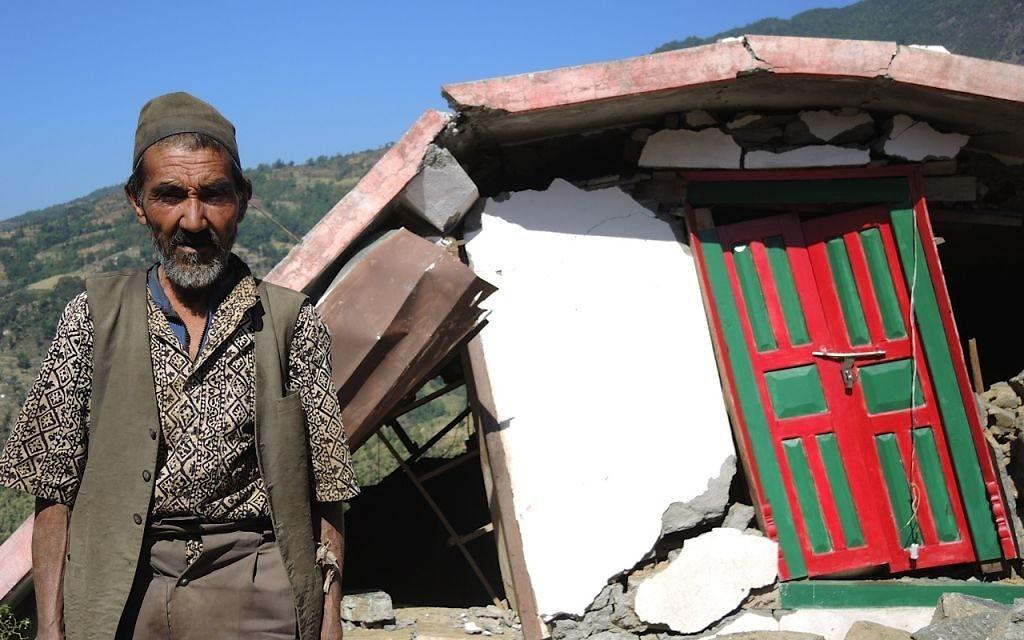 Un homme se tient à l'extérieur des ruines de sa maison à 2 heures de marche de Topani, dans le district de Sidhulpalchowk au nord-est de Katmandou au Népal, mai 2015 (Crédit : Melanie Lidman / Times of Israël)