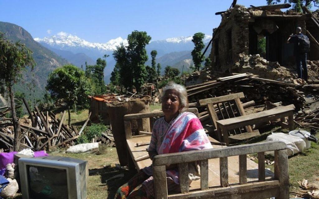 Une femme est assise avec les choses récupéréss de son domicile dans le village de Topani au Népal. Les villages avaient de l'électricité provenant d'un barrage hydroélectrique dans la rivière, mais il faudra probablement mois avant que l'électricité ne soit restauré dans cette région, mai 2015 (Crédit : Melanie Lidman / Times of Israël)
