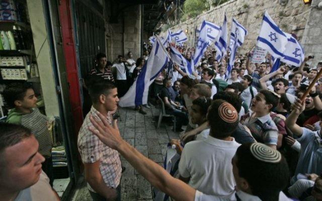 De jeunes israéliens devant un magasin arabe de la Vieille Ville au cours de la marche des drapeaux du Jour de Jérusalem, le 21 mai 2009. (Crédit : Abir Sultan / Flash90)