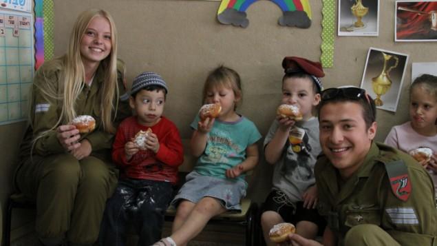 Des soldats qui envisagent  une conversion en visite dans un jardin d'enfants à Efrat, pour Hannukah, le 7 novembre 2013 (Crédit : Gershon Elinson /Flash 90)