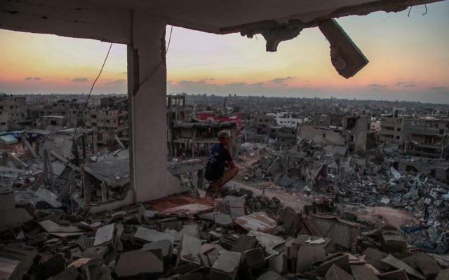 Un homme est assis dans une maison détruite dans le quartier Al Shejaeiya dans l'est de la ville de Gaza, le 28 août 2014 (Crédit : Emad Nassar/Flash90)