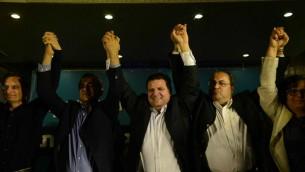 Le dirigeant de la liste (arabe) unie Ayman Odeh (centre) réagit avec d'autres membres du parti au siège du parti à Nazareth à l'annonce des sondages de sortie des élections le 17 mars 2015 (Crédit : Basel Awidat / Flash90)