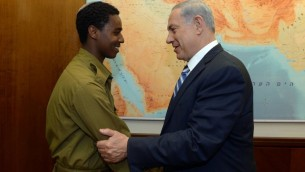 Le Premier ministre Benjamin Netanyahu rencontre Damas Pakada, le soldat éthiopien israélien qui a été agressé par des policiers, au bureau du Premier ministre, à Jérusalem, le 4 mai 2015 (Crédit : Haim Zach / GPO)