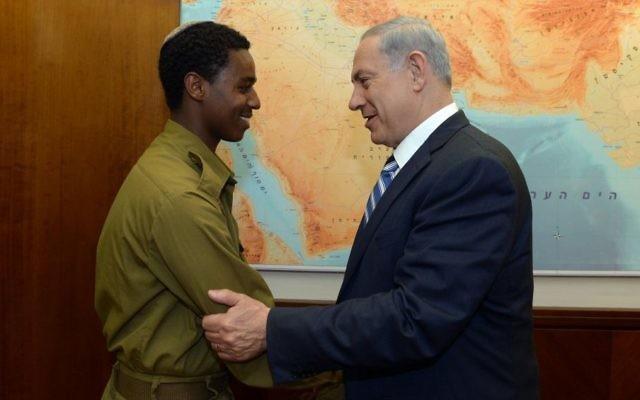 Le Premier ministre Benjamin Netanyahu rencontre Damas Pakada, le soldat éthiopien israélien qui a été agressé par des policiers, au bureau du Premier ministre, à Jérusalem, le 4 mai 2015 (Crédit : Haim Zach/GPO)